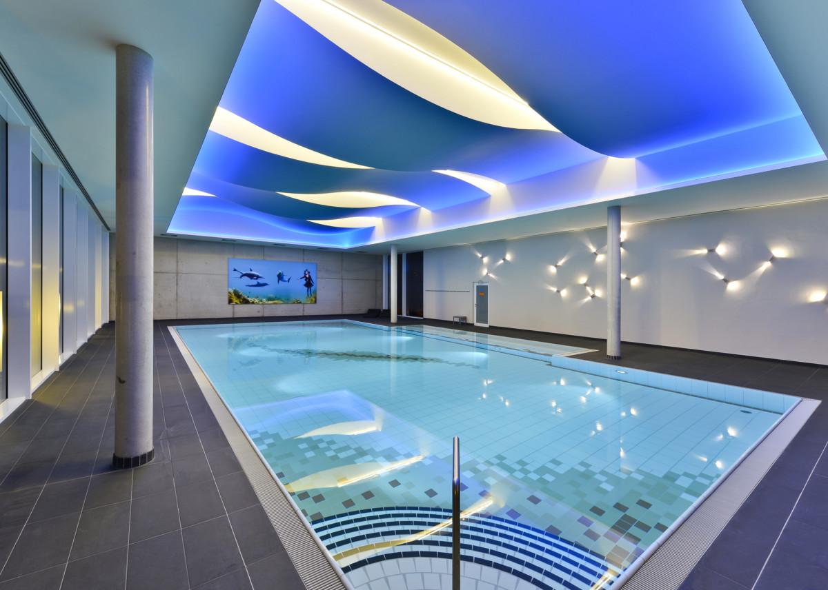 Innenausbau eines Schwimmbads mit Powerpanel H2O. Die speziellen wasserfesten, faserarmierten Zementplatten wurden auch für die Deckengestaltung mit unterschiedlich runden Formen eingesetzt, die das Wellenbild des Wassers spiegeln